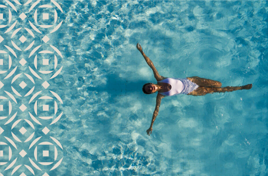 overhead photo of woman in white swimsuit floating in pool with white circle and diamond pattern overlaying the left third of the image